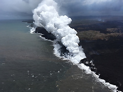 "Handout photo of KÄ«lauea Volcano — Ocean Entry and Laze. An aerial view, looking west, of the two active ocean entries on KÄ«lauea Volcano's lower East Rift Zone. The large white plume (foreground) is the eastern ocean entry; the weaker, western plume can be seen in the distance. The white plume, referred to as ""laze,"" is a mixture of condensed acidic steam, hydrochloric acid gas, and tiny shards of volcanic glass that can irritate lungs, eyes and skin. May 26, 2018. Photo by USGS via ABACAPRESS.COM"