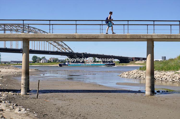 Nederland, nijmegen, 5-8-2020 Opnieuw komt er een periode van droogte en hoge temperatuur, hittegolf . Deze kleine nevengeul in de Waal is goeddeels drooggevallen. Recreanten zijn via het bruggetje op weg naar het waalstrand . Vooral jonge mensen zoeken verkoeling aan de oevers van de waal op deze tropisch warme nazomerdag . Het is eigenlijk verboden in de rivier te zwemmen vanwege de stroming en het drukke scheepvaartverkeer . Deze strandje liggen tussen de kribben in de Stadswaard . Staatsbosbeheer heeft de bedding met draad afgesloten zodat de wilde konikpaarden en runderen niet tussen de mensen in de stadswaard terecht komen. Vorig jaar moesten enkele paarden uit de kudde genomen worden omdat ze teveel door mensen waren gevoerd en aangehaald.Foto: ANP/ Hollandse Hoogte/ Flip Franssen