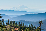 Mount Rainier (14,411 feet) rises 100 miles south of a hike on Three Fingers Mountain in Boulder River Wilderness on Goat Flats Trail #641 from Tupso Pass trailhead to Tin Can Gap, Washington, USA.