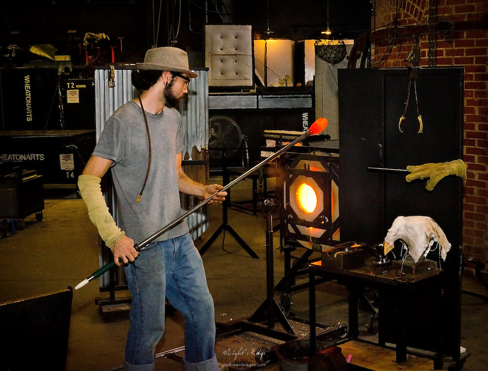 An artisan pulls a fresh gather of glass out of the glory hole at Wheaton Arts.