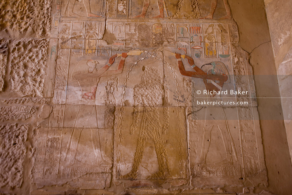 A detail of a defaced Queen Hatshepsut in temple of Amun at Karnak at the Temple of Amun at Karnak, Luxor, Nile Valley, Egypt. Queen Hatshepsut reigned from 1473 to 1458 BC but her successor Tuthmosis III quashed an Asiatic uprising and records of Hatshepsut disappeared. Tuthmosis III was finally able to claim his rightful place as King of Egypt and all images of Hatshepsut were attacked; statues, reliefs and shrines all were defaced. While the queen was damaged, the Gods either side in this painting were left untouched. <br /> <br /> <br /> <br /> <br /> <br /> The records of Hatshepsut were erased but no-one knows why. The Karnak Temple Complex is the largest religious building ever made, covering about 200 acres. It comprises a vast mix of decayed temples, chapels, pylons, and other buildings built over 2,000 years and dedicated to the Theban triad of Amun, Mut, and Khonsu.