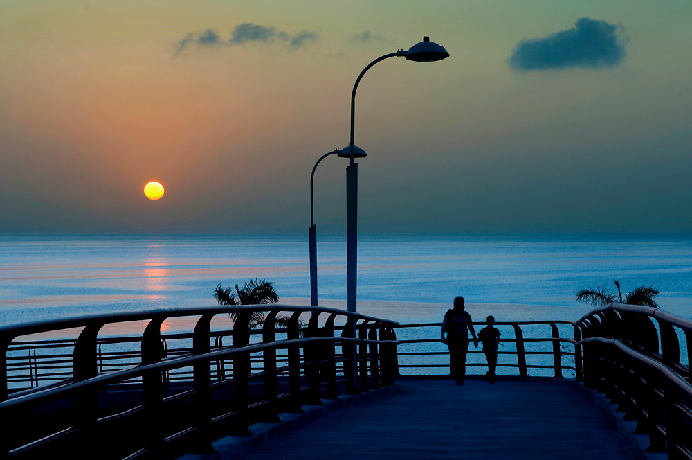 Sun rises over the Pacific Ocean as a mother and son walk over a pedestrian bridge, allowing residents of Panama City, Panama to walk over busy Balboa Avenue.