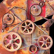 An old rustic hay bailer, filled with wheels, gears and chain belts, creates an abstract image. The bailer was found in a ghost town in northern Arizona. Colin Braley/Wild West Stock
