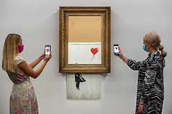 """© Licensed to London News Pictures. 03/09/2021. LONDON, UK.  **UNDER EMBARGO UNTIL FRIDAY 3 SEPTEMBER 2021, 12PM BST** Staff photograph """"Love Is in the Bin"""" by Banksy at a preview at Sotheby's.  The painting, originally known as """"Girl with Balloon"""", was famously shredded by the artist in Sotheby's London auction room in 2018 after being sold for £1,042,000.  The resulting artwork was later renamed """"Love Is in the Bin"""" and will be offered for sale in Sotheby's contemporary art evening auction on October 14 with an estimate of £4-6 million.  Photo credit: Stephen Chung/LNP"""
