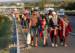 © London News Pictures. 04/09/2015. Bicske, Hungary. Hundreds of migrants walk along the the motorway from Budapest north towards Austria September 4, 2015.  Picture by Paul Hackett/LNP