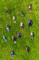 Aerial view of yoga group exercising in park.