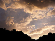 A rocky ridge makes a silhouette against clouds and blue sky at sunset. Valley of Fire State Park, dedicated in 1935, is the oldest state park in Nevada.