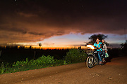 29 JUNE 2013 - BATTAMBANG, CAMBODIA:  A motorcycle goes down a rural dirt road at the sun sets over a rice field near Battambang, Cambodia.   PHOTO BY JACK KURTZ