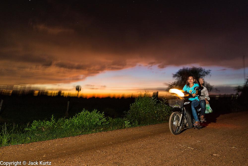 29 JUNE 2013 - BATTAMBANG, CAMBODIA:  A motorcycle goes down a rural dirt road at the sun sets over a rice field near Battambang, Cambodia.   PHOTO BY JACK KURTZ