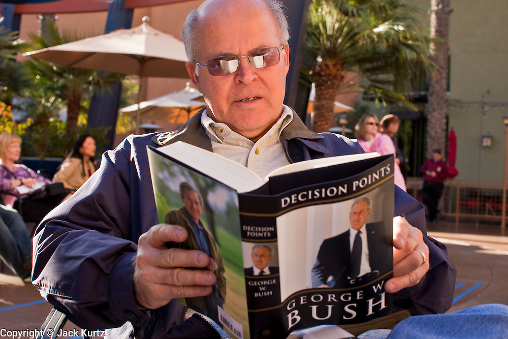 """09 DECEMBER 2010 - PHOENIX, AZ: PAUL TELLEZ, from Phoenix, reads George W. Bush's book, """"Decision Points"""" after waiting for more than five hours to get an autographed copy at the Barnes & Noble Bookstore in Phoenix, AZ, Thursday, Dec. 9. More than 2,000 people lined up starting at 5AM to get copies of the former President's book, """"Decision Points."""" A handful of protesters demonstrated against President Bush near the bookstore, calling him a """"war criminal.""""   PHOTO BY JACK KURTZ"""