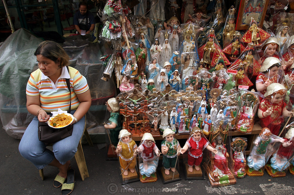 """A woman eats pancit (noodles) as she waits for buyers of any of her hundreds of Santo Niño and other religious statues during the Philippines festival of the Santo Niño. Many Filipinos in this predominantly Catholic population have similar statues, which they parade through the streets once a year. The tourism department of the Philippines calls Metro Manila's Santo Niño Festival """"a grand procession of over 200 well-dressed images of the child Jesus."""" (Supporting image from the project Hungry Planet: What the World Eats) The family of Angelita Cabaña of Manila has their own Santo Niño statue in the living room of their small home."""