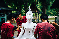 A monk and drug rehab patients work to put together a stone Buddha statue at one of Tham Krabok's many workshops. The temple provides these statues to other monasteries throughout Thailand.