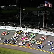 NASCAR drivers go four wide into turn 1 during the NASCAR Coke Zero 400 Sprint series auto race at the Daytona International Speedway on Saturday, July 6, 2013 in Daytona Beach, Florida.  (AP Photo/Alex Menendez)