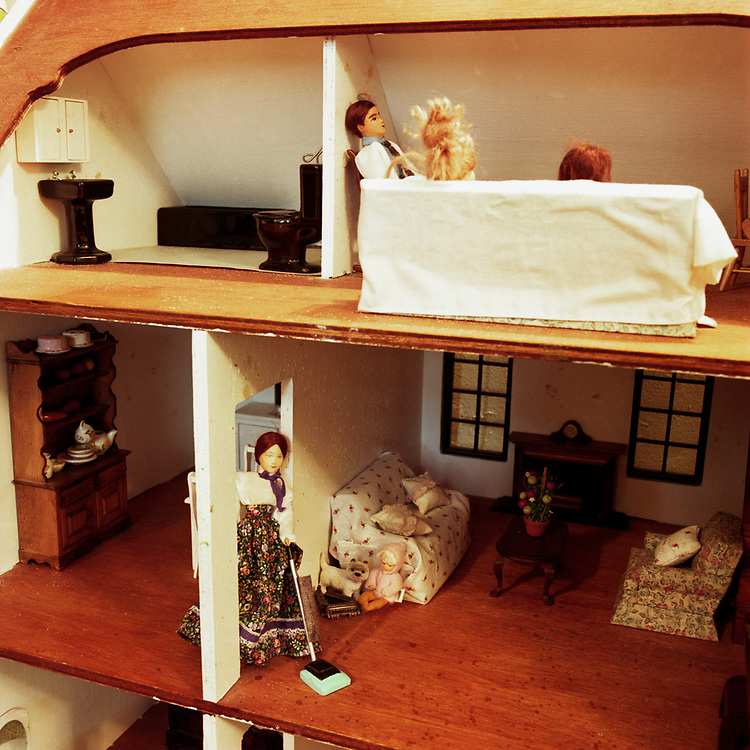 Looking into a dollhouse from the outside. There is a mother on the main floor cleaning the floor with a push vacume while the father and 2 daughters are directly above on the top floor sitting on a chair and couch, perhaps watching TV and chatting.