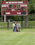 Cornwall-on-Hudson, New York - Three women stand in front of the scoreboard as New York Military Academy plays the Harvey School in a football game on Oct. 17, 2009.
