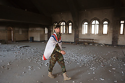 © Licensed to London News Pictures. 04/11/2016. Hamdaniyah, Iraq. A Christian militiaman, wrapped in the Assyrian flag, walks through the fire damaged Syriac Catholic Church of Mar Behnam and his sister Mart Sarah in the recently liberated Christian town of Hamdaniyah, Iraq. The church was vandalised and burnt by Islamic State militants during their two year occupation of the town which was retaken by Iraqi Security Forces during the ongoing Mosul Offensive.<br /> <br /> Although located close to a front line, littered with improvised explosive devices and pieces of unexploded ordnance the Christian town of Hamdaniyah has only recently been cleared of ISIS extremists who stayed behind to fight. After the town's liberation as part of the Mosul Offensive residents and priests of the town are now free to take short trips to assess damage, salvage possessions and clear up the mess left by militants during their two year occupation.<br /> <br /> Hamdaniyah, and much of the Nineveh plains, were captured by the Islamic State during a large offensive on the 7th of August 2014 that saw the extremists advance to within 20km of the Iraqi Kurdish capital Erbil. Residents of the town, who included many Christian refugees who escaped there after the fall of Mosul, were then forced to seek sanctuary in the Kurdish areas. In the year and two months of the ISIS occupation churches were burnt, homes were put into use as militant accommodation and bomb factories and some buildings destroyed by coalition airstrikes. Photo credit: Matt Cetti-Roberts/LNP