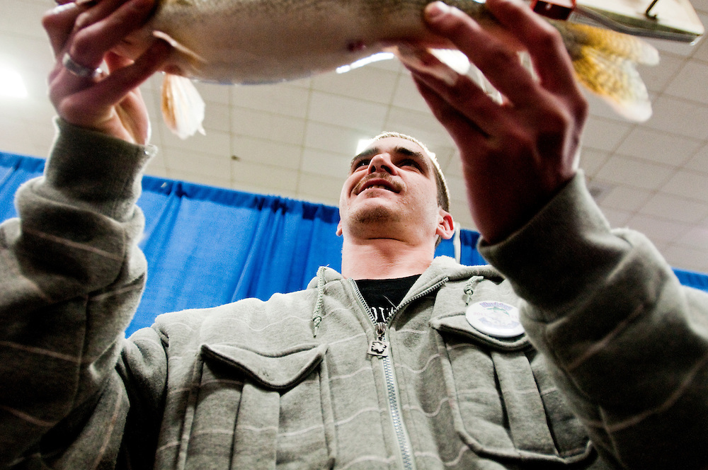 Matt Dixon   The Flint Journal..Frankie Dean of Flint shows his biggest walleye to the crowd during Flushing's 11th Annual Walleye Festival, Saturday, March 12.