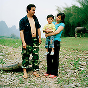Huang Jen, a soldier, 24 and his wife Ha Ping, also 24 have a daughter Huang She, 2. They are pictured here on the banks of the River Li, in Fulli Town Village, Guangxi province. Because they had a girl first and live in the countryside, they will be able to try for another baby when their daughter is two...Its over thirty years (1978) since the Mao's Chinese government brought in the One Child Policy in a bid to control the world's biggest, growing population. It has been successful, in controlling growth, but has led to other problems. E.G. a gender in-balance with a projected 30 million to many boys babies; Labour shortages and a lack of care for the elderly.