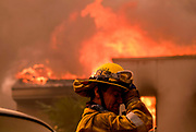 A firefighter keeps watch the Woolsy fire burning a home near Malibu Lake in Malibu, Calif., Friday, Nov. 9, 2018.