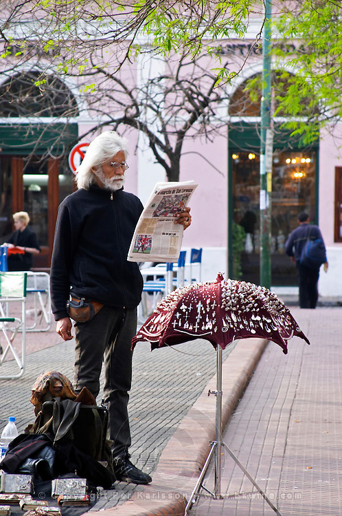 in the San Telmo district around Plaza Dorrego Square, on the square a man in black with a white beard and long white hair selling small jewellery and pins from a stand that looks like an umbrella Buenos Aires Argentina, South America