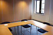 Vacant desks and empty chairs are placed facing each other for an Ernst & Young's counselling workshop held for company employees at Prospect House, Borough, Southwark, London. Soon, employees of this seminar will arrive for a day's role-playing in this classroom setting where the office furnature makes a square to force participants to confront their opposite numbers. Jotter pads are provided for brainstorming ideas and concepts that help E & Y get the best out of their talented people. The room is otherwise empty as bright daylight floods through a window allowing positive thoughts and bright ideas to influence their thinking.