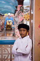 Young Cao Dai boy inside the Great Divine Temple.