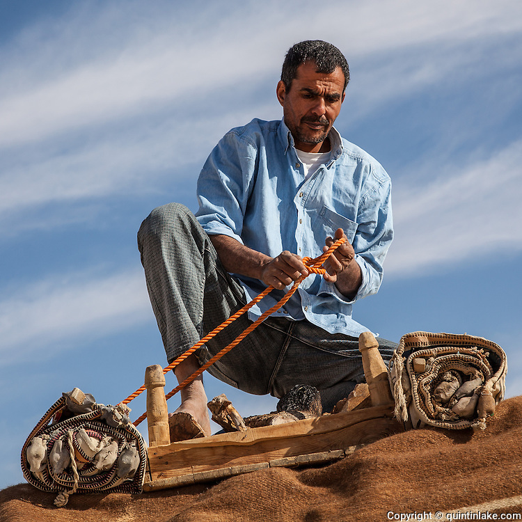 Khaled ties camping equipment to the top of the Landcruiser. Western Desert, Egypt