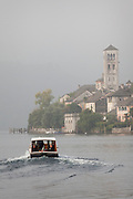 Passengers ride a ferry boat to the island monastery on Isola San Giulio on Lake Orta, Piedmont, Italy.
