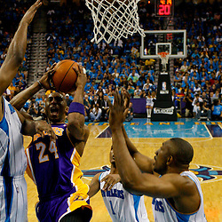 April 28, 2011; New Orleans, LA, USA; Los Angeles Lakers shooting guard Kobe Bryant (24) shoots between New Orleans Hornets power forward Carl Landry (24) and small forward Trevor Ariza (1) and center D.J. Mbenga (28) during the third quarter in game six of the first round of the 2011 NBA playoffs at the New Orleans Arena. The Lakers defeated the Hornets 98-80 to advance to the second round of the playoffs.   Mandatory Credit: Derick E. Hingle