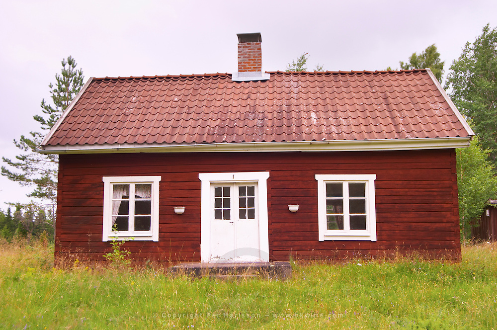 Traditional style Swedish wooden painted house. Overgrown unkempt garden. Smaland region. Sweden, Europe.