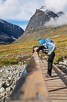 Female hiker leans on bridge in Ladtjovagge with Tolpagorni - Duolbagorni mountain in distance, Lappland, Sweden