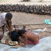 Children of a duck farmer play during down time on the farm in a village at the base of Phnom Krom, just outside of Siem Reap, Cambodia; none of them has ever attended school, as their family cannot afford to spare the additional income that sending them to school would forgo.