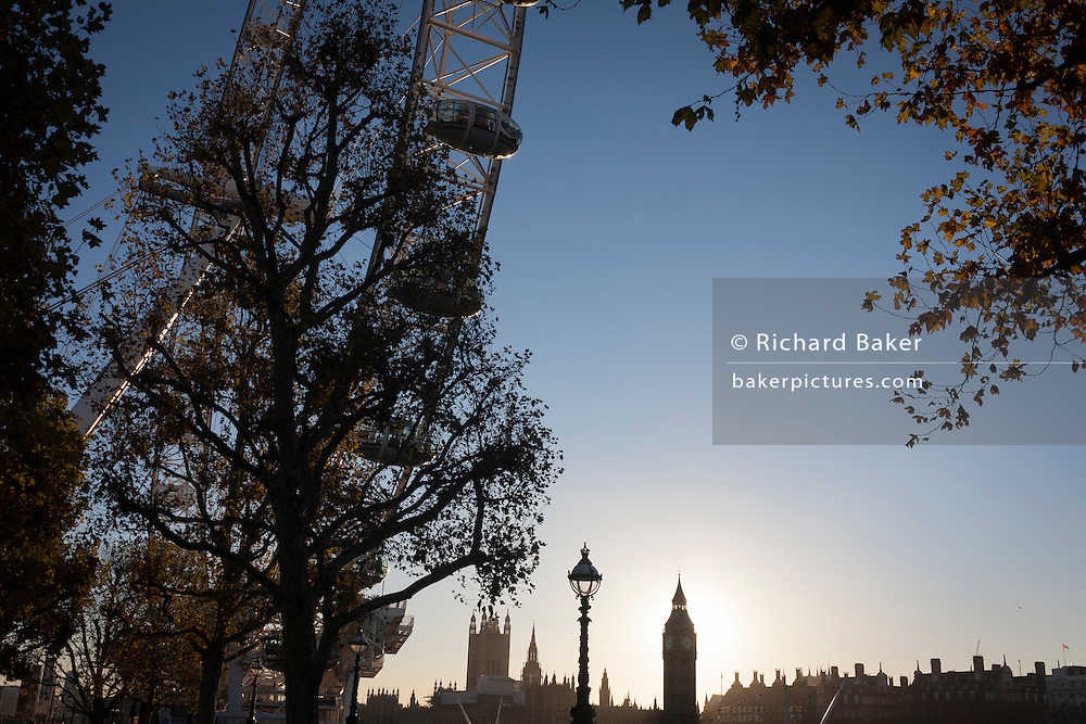 The London Eye ferris wheel and in the distance, the Houses of Parliament and Big Ben, on 29th November 2016, on the Southbank in London, England.