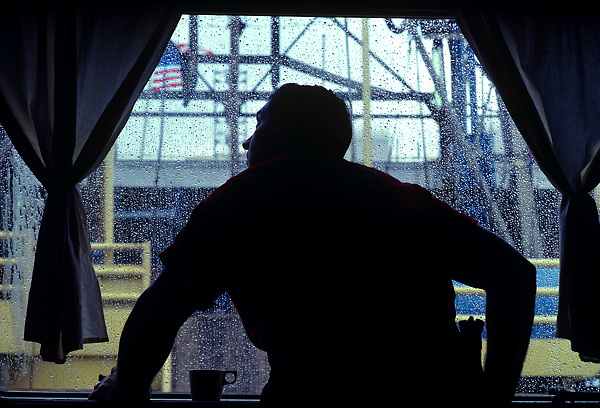 Stock photo of a man looking out a window at a rig