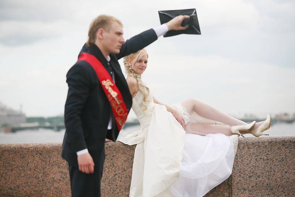 A Russian groom helps out his photographer on the Neva River, St. Petersburg