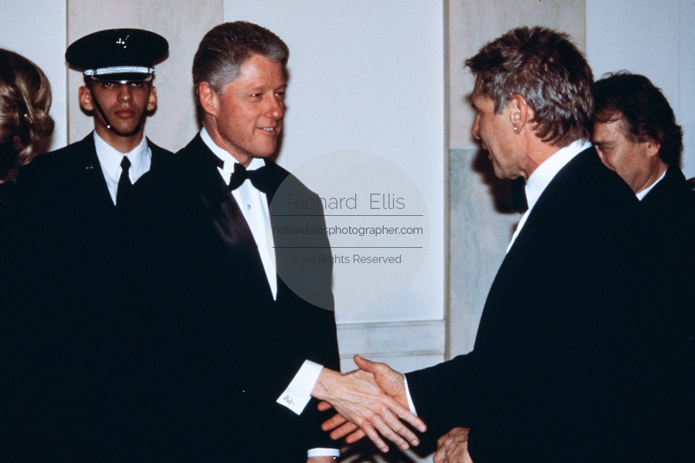 U.S. President Bill Clinton, left, welcomes actor Harrison Ford in the receiving line during the State Dinner at the White House February 5, 1998 in Washington, DC.