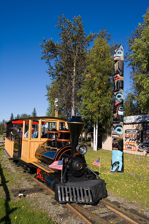 The small gauge Crooked Creek and Whiskey Island Railroad passes by a totem pole outside the Alaska Native Village display and  is a popular attraction for young and old to ride around the grounds of Pioneer Park in Fairbanks, Alaska
