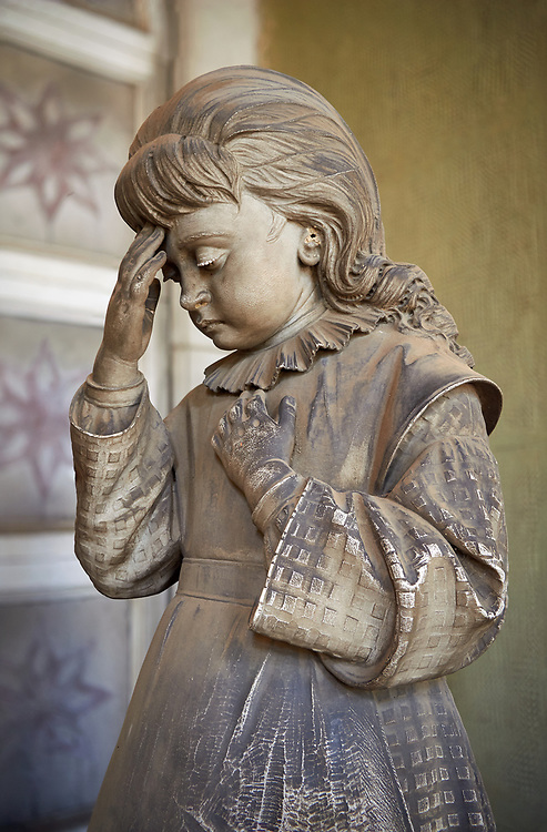Picture and image  of the Realistic young grieving girl stone funary monument sculpture  commissioned by Enrico Amerigo for his sisters memory. beside the pedestal on which the sculptor set the deceased's bust he placed, on the left, the figure of an old blind man, kneeling down and leaning on a stick; on the right he placed the figure of a young orphan girl, recognizable as such by her kindergarten uniform, portrayed in the act of making the sign of the cross. This work belongs to the Realism, a trend which was typical during the 1880s and 1890s, according to which the orphans, the poor, the sick and all those who benefited from somebody's generosity had to be portrayed in a concrete fashion. Sculptor G Moreno 1890. Section A, no 53, The Staglieno Monumental Cemetery, Genoa, Italy .<br /> <br /> Visit our ITALY PHOTO COLLECTION for more   photos of Italy to download or buy as prints https://funkystock.photoshelter.com/gallery-collection/2b-Pictures-Images-of-Italy-Photos-of-Italian-Historic-Landmark-Sites/C0000qxA2zGFjd_k<br /> If you prefer to buy from our ALAMY PHOTO LIBRARY  Collection visit : https://www.alamy.com/portfolio/paul-williams-funkystock/camposanto-di-staglieno-cemetery-genoa.html