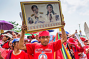 06 APRIL 2014 - BANGKOK, THAILAND:  A  man holds up photos of Thaksin Shinawatra, the exiled former Prime Minister of Thailand and Yingluck Shinawatra, the current Prime Minister and Thaksin's sister. Red Shirts and supporters of the government of Yingluck Shinawatra, the Prime Minister of Thailand, gathered in a suburb of Bangkok this weekend to show support for the government. The Thai government is dealing with ongoing protests led by anti-government activists. Legal challenges filed by critics of the government could bring the government down as soon as the end of April. The Red Shirt rally this weekend was to show support for the government, which public opinion polls show still has the support of most of the electorate.  PHOTO BY JACK KURTZ