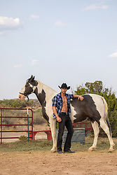 hot cowboy with open shirt leaning on a paint horse