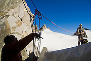 Climbers Brian Polagye, left, and Jim Prager struggle with a knot formed in their rope during a traverse of the Eldorado Ice Cap in the heart of North Cascades National Park, Washington.
