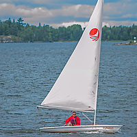 A sailor navigates a small boat similar to a Laser on Lake of the Woods, near Kenora, Ontario, Canada.