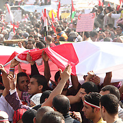 Young Egyptians work together to pass a massive national flag over their heads in Tahrir Square during the Day of Justice and Cleansing.