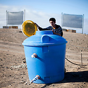 Nicolas Prado of the Universidad Catolica, .  checks the water level of a tank that stores water collected from fog catching nets Alto Patache fog Oasis near Iquique in Northern Chile.