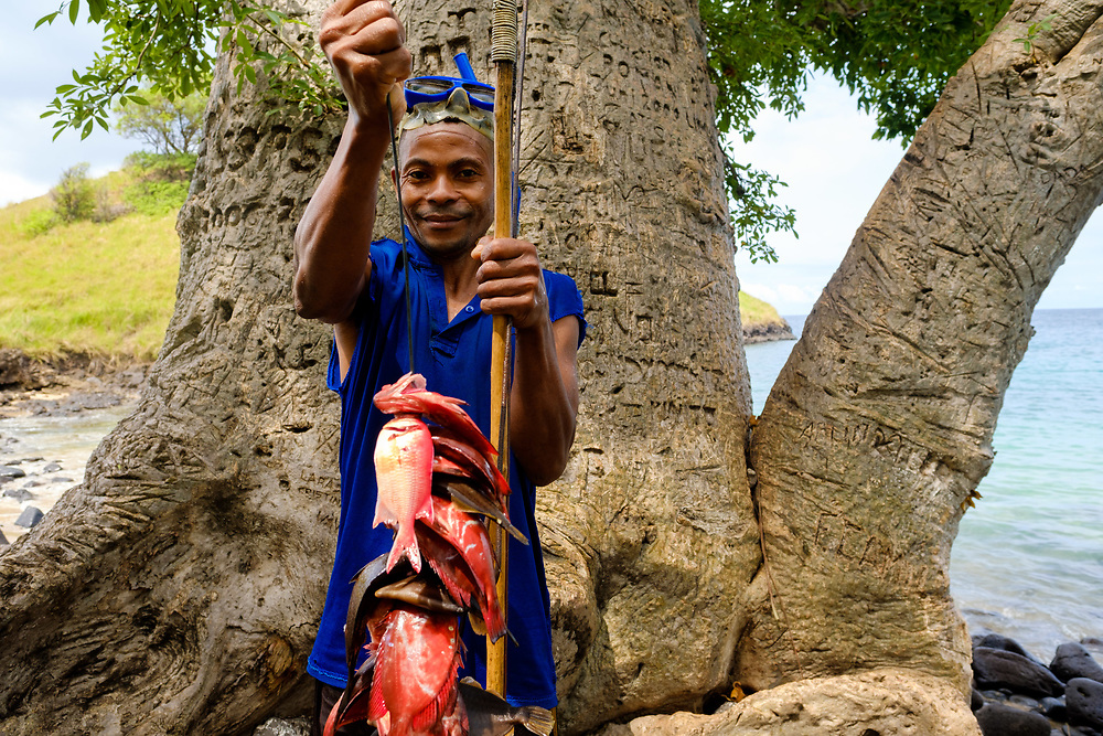 A fisherman showing his catch near Lagoa Azul (Blue Lagoon) , in São Tomé island.