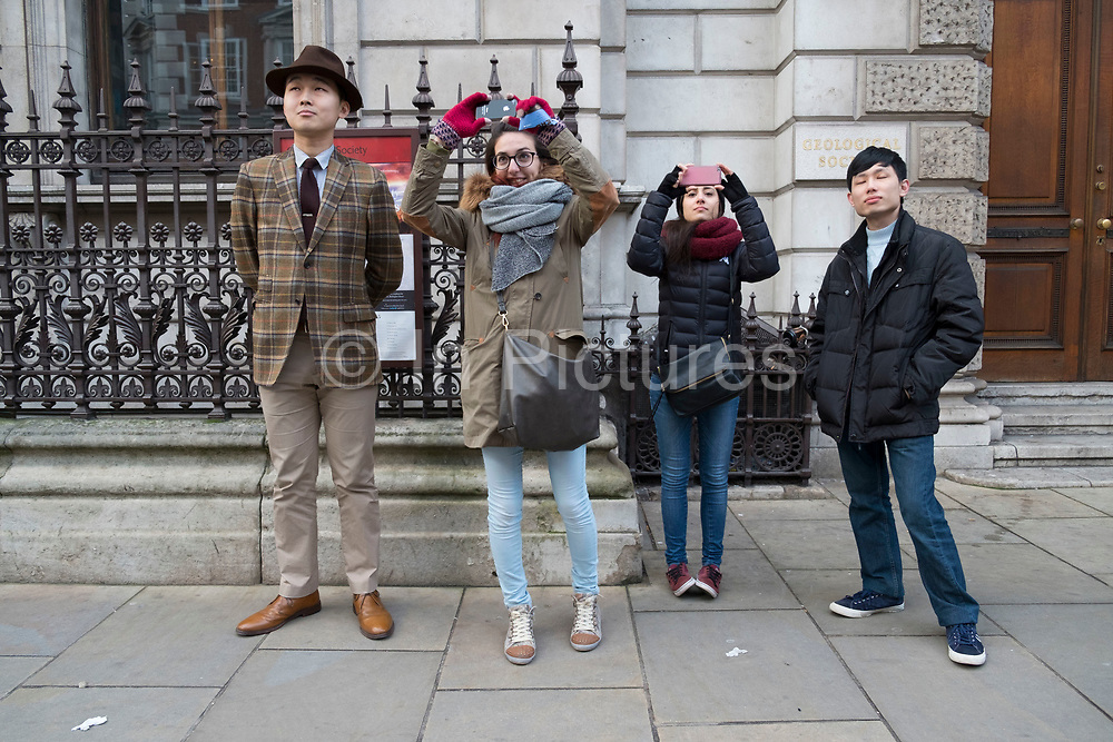 International tourists including one Chinese man dressed in a very traditonal English suit and hat standing looking up and taking pictures of the Fortnum & Mason clock on Piccadilly in London, England, United Kingdom. The clock was added to the front of the Piccadilly building in 1964, and the two men represent the store's founders, Mr Fortnum and Mr Mason, who appear once an hour. (photo by Mike Kemp/In Pictures via Getty Images)