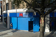 A man wearing a face covering stands outside a branch of Metro Bank that is undergoing refurbishment on the King's Road in Chelsea, during the second wave of the Coronavirus pandemic, and when the capital is designated by the government as a Tier 2 restriction, on 20th October 2020, in London, England.