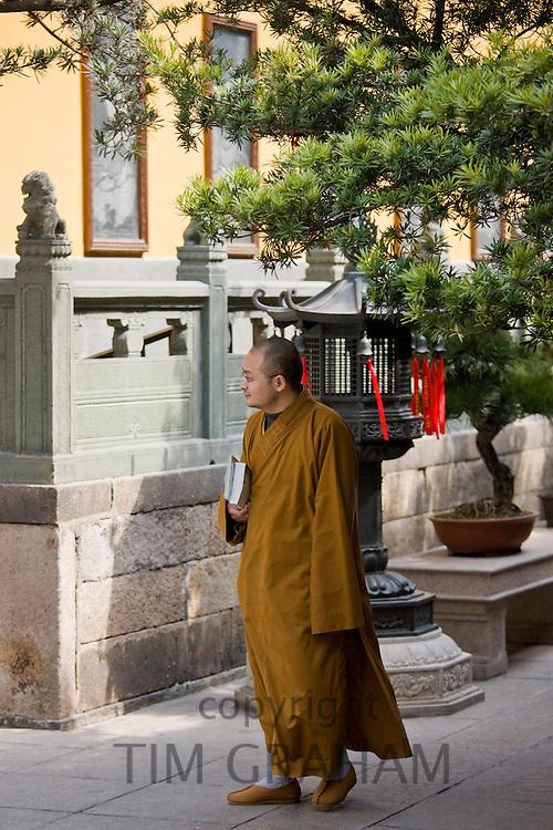 Buddhist monk in saffron robes at the Jade Buddha Temple, Shanghai, China