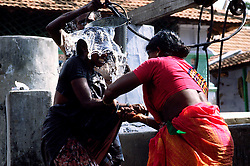TAMIL NADU, MARCH 1994.A woman is restraining her daughter who is in chains. Meanwhile her father is throwing a bucket of water from the well over her body. This is meant to clean her from the evil spirits believed to possess her body..