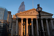 With modern offices of financial institutions behind, an architectural sunlit view of the friezes and Latin inscriptions on the pediment of the Royal Exchange in the City of London, the capital's financial district, on 27th February 2021, in London, England. At the top of Doric and Ionic columns with their ornate stonework, powerfully strong lintels cross, bearing the load of fine artistry and carvings which feature the design by Sir William Tite in 1842-1844 and opened in 1844 by Queen Victoria whose name is written in Latin (Victoriae R). It's the third building of the kind erected on the same site. The first Exchange erected in 1564-70 by sir Thomas Gresham but was destroyed in the great fire of 1666. It's successor, by Jarman, was also burned down in 1838. The present building is grade 1 listed and cost about £150,000.